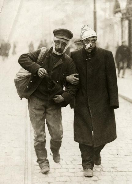A wounded German soldier and a wounded Belgian soldier walk arm in arm down a street, 1915.