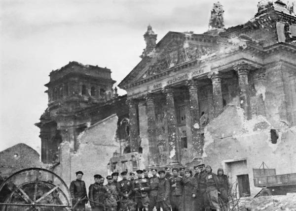 Red Army soldiers pose in front of the Reichstag 1945